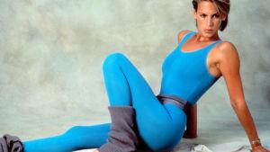 Kvinna sitter på golvet i blåa träningstrikåer