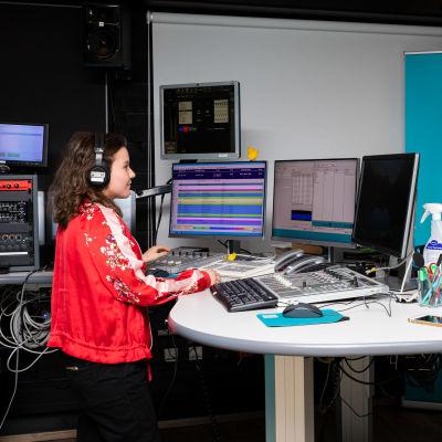 Nainen ja mies seisovat vastakkain eri puolilla radion lähetyspöytää ja katsovat toisiaan.