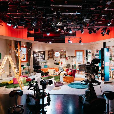 tv-studiossa lastenohjelman kulissit, etualalla tv-kameroita, katossa ja sivuilla valaisimia