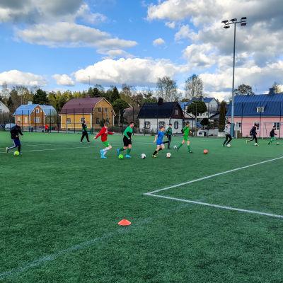 Ett tiotal pojkar på en konstgräsplan under en fotbollsträning.