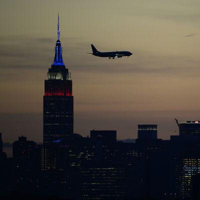 New Yorks och ett flygplans siluett mot solnedgången.