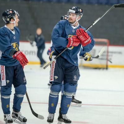 Sakari Salminen och Jesse Joensuu samtalar på isen. Joensuu (t.h.) har klubban i vädret.