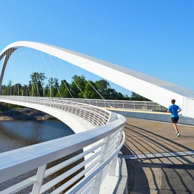 En man joggar på bron till Blåbärslandet.