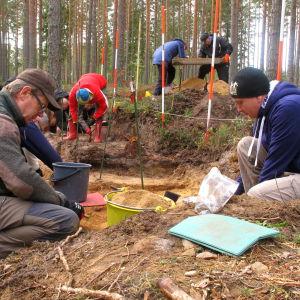 Flera personer sitter på huk vid ett arkeologiskt utgrävningsområde.