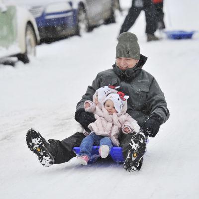 En man håller i ett litet barn medan de åker pulka ner för en backe.