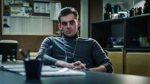 Sakari Nurmi istuu vakavannäköisenä työpöytänsä ääressä. Kaulassa roikkuu virkamerkki.