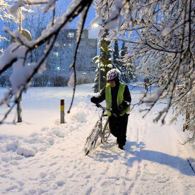 En cyklist leder sin cykel i snön.