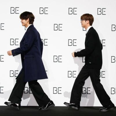 Kolme nuorukaista kävelee peräkkäin lavalla.