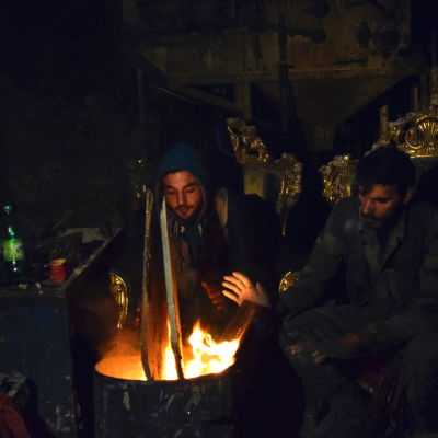 Syriska regeringstrogna soldater värmer sig vid en lägereld  i Aleppo den 29 december 2016.