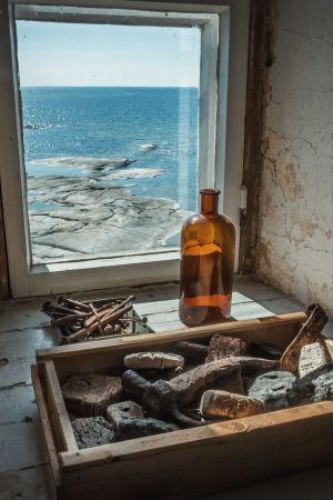 Ikkunanlaudalla ruskea lasipullo, laatikollinen kiviä ja rasia, jossa vanhoja nauloja. Ikkunasta merinäköala, sää aurinkoinen.