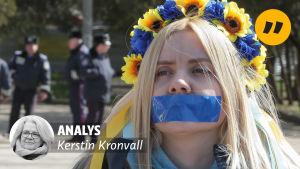 En ukrainsk kvinna med blågul krans i håret och en blå tejpbit på munnen.