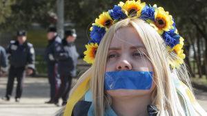 En kvinna med blå tejp för munnen under en protest mot minskad yttrandefrihet i Ukraina 2014.
