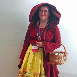 Punaiseen asuun kirjanoidaksi pukeutunut Anne Leinonen poseeraa Woldcon tapahtumassa.