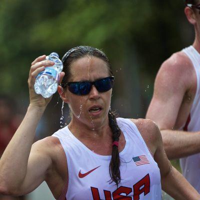 Erin Talcott häller vatten över sitt huvud under ett lopp.