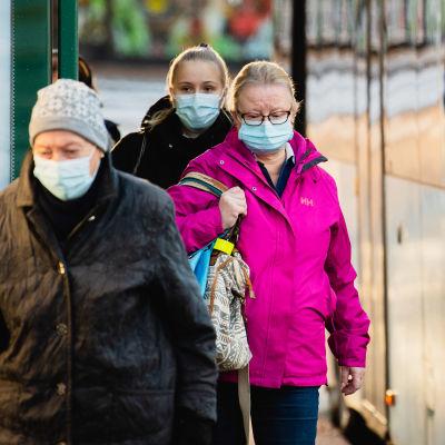 Ihmisiä hengityssuojaimet kasvoilla bussipysäkillä Sörnäisissä.