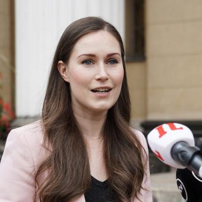 Kvinna i ljus kavaj och långt, brunt hår står ute intill flera mikrofoner. Statsminister Sanna Marin utanför Ständerhuset i Helsingfors den 15 september 2020.