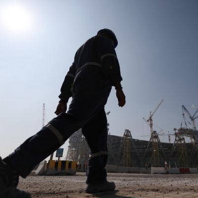 Migrantarbetare traskar vid stadionbygge i Qatar.