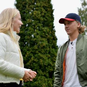 En blond flicka och en pojke med keps står och pratar med varandra. Bilden är tagen snett nerifrån och i bakgrunden finns gröna träd.