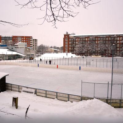 Ishockeyrink och skridskobana i en stad med höghus i bakgrunden.