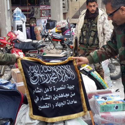 Syriska soldater håller upp en flagg som tillhört jihadistgruppen Jabhat al-Nusra.