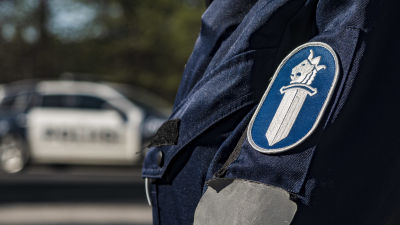 Närbild av polisens logo på en polisuniform. I bakgrunden syns en polisbil.