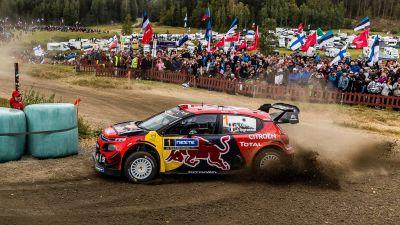 En rallybil kör i en kruva inför publik.