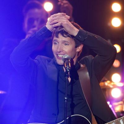 En man står på en scen med händerna ovanför huvudet.