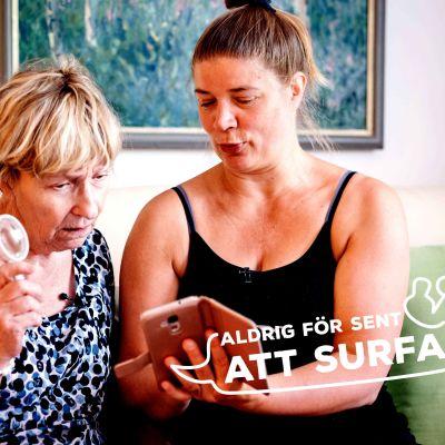 Yngre kvinna lär en äldre kvinna att använda mobiltelefonen.