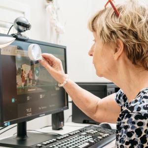 Nainen katsoo suurennuslasilla tietokoneen näyttöä.