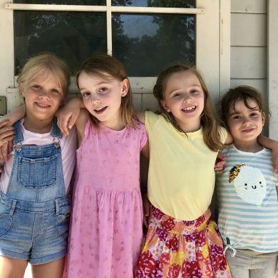 Fyra glada småflickor står med armarna om varandras axlar framför en trävägg.