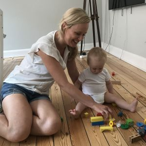 Karin Hafstad bygger med klossar på golvet med sin 1-åriga son.