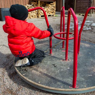 Ett barn i tjock röd jacka på en karusell i en lekpark.