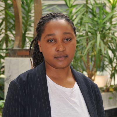 mörk ung kvinna framför krukväxt