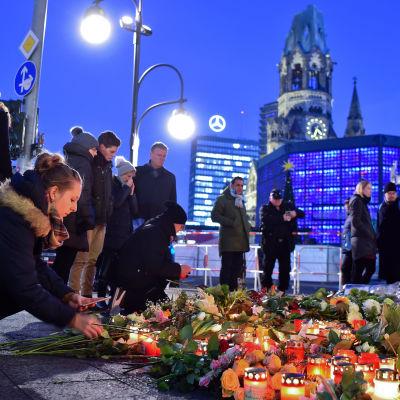 Blommor och ljus vid julmarknaden i Berlin där 12 människor dog i ett terrorattentat.