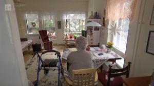 Äldre ensam kvinna tittar ut i vardagsrummet.