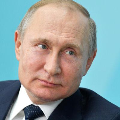 Närbild av Vladimir Putin som tittar åt sidan medan han böjer sig framåt något. Turkos bakgrund.