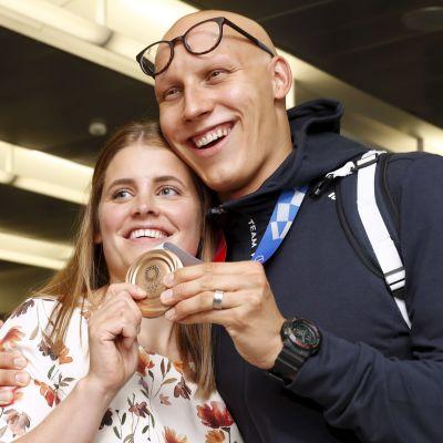 Matti Mattsson visar upp sin bronsmedalj tillsammans med frun Maiju.