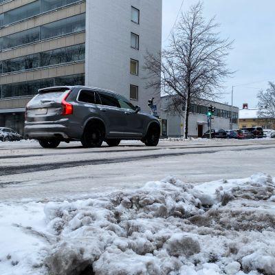 Auto ajaa Turun keskustassa lumisella tiellä.