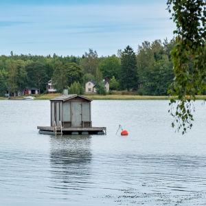 En bastubyggnad på pontoner flyter på vattnet, förtöjd vid en boj.