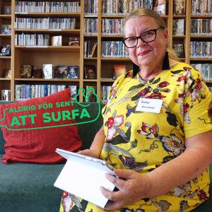 """Ritva Kämäri sitter på en soffa framför en bokhylla och håller i en pekplatta. Hon ler och har på sig en gul, blommig klänning. På bilden finns också en logga med texten """"Aldrig för sent att surfa""""."""