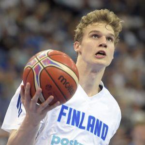 Basketspelaren Lauri Markkanen i farten med bollen i högsta hugg.