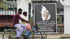 Cyklister på Sri Lanka vid en plansch som visar fyra händer med olika religiösa symboler