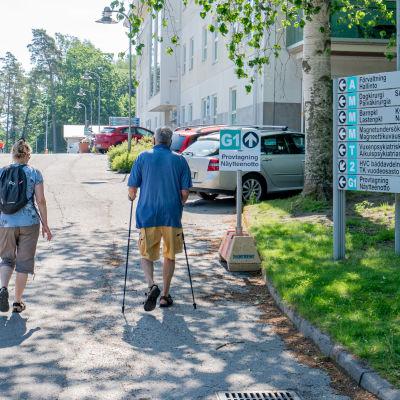 Raaseporin sairaalan kyltti ja kaksi kävelijää.