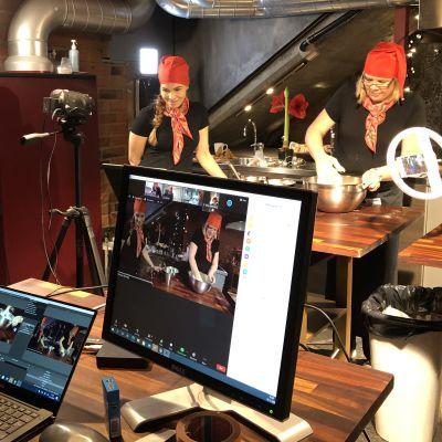 Kamera kuvaa kahta naista, jotka ohjaavat pikkujoulutapahtumaa verkossa.
