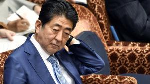 Japans premiärminister ser orolig ut vid ett krismöte efter att Nordkorea avfyrade en missil som landade utanför den japanska kusten.