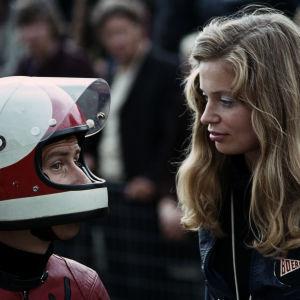 Jarno Saarinen med motorcykelhjälm på huvudet pratar med sin hustru Soili Saarinen med långt blont hår.
