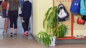 En bild på barn som går i en korridor. Där finns en grön växt och en klädhängare.