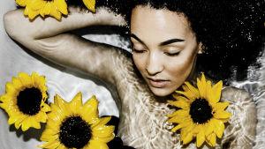 Nainen makaa vesialtaassa silmät kiinni pidellen toista kättään päänsä takana. Hänellä on mustat afrokiharat. Vedessä kelluu auringonkukkia.
