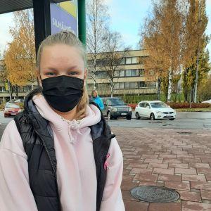 Kvinna står på parkering med butikskasse.