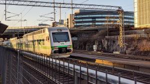 Ett lokaltåg kör i soluppgången förbi Kottby station i Helsingfors.